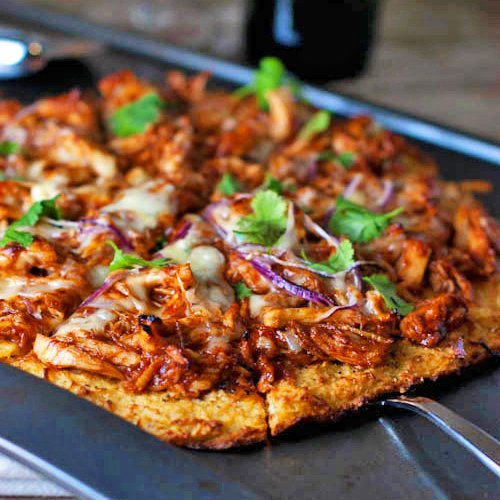 Close up of sliced BBQ chicken pizza on a pan