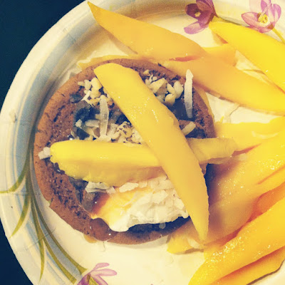 A paper plate with a gingerbread cookie and slices of mango