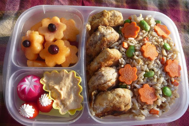 A bento lunch idea, with melon shaped like flowers, meat and carrots shaped like carrots in rice