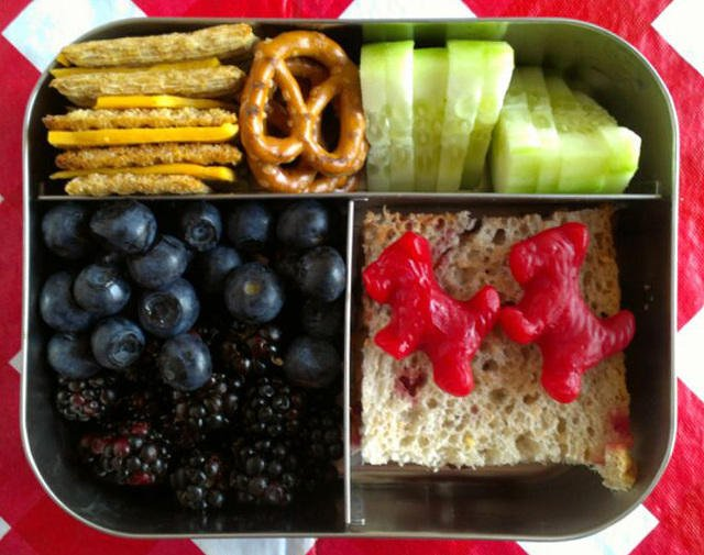Bento lunch idea with crackers, pretzels, cucumber slices, blueberries, blackberries and bread