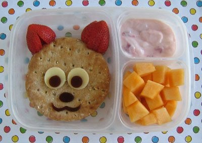 A bento box with a sandwich shaped cat using strawberries for ears, yogurt and cheese squares