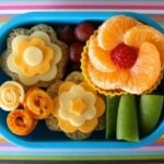 A bento lunch; sandwiches and fruit laid out to look like flowers