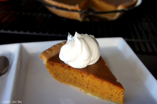 A slice of pumpkin pie on a plate with whipped cream on top