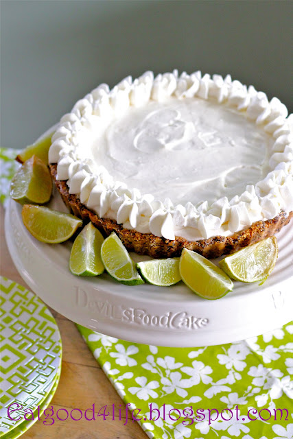 A close up a of a No Bake Key Lime Pie topped in a white topping and sliced limes  on the side