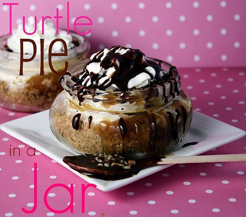 Frozen Turtle pie in a small mason jar topped with drizzled chocolate topping on a white square plate