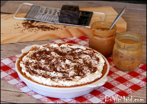 English Banofee pie  on top of a red checkered cloth next to a jar of caramel