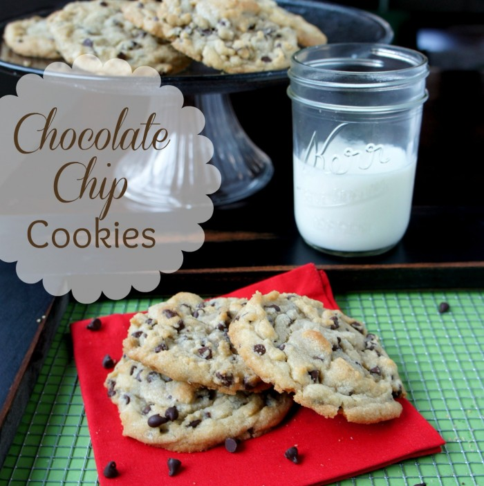 A display of chocolate chip cookies on a napkin with a side of a glass of milk next to a platter with more cookies
