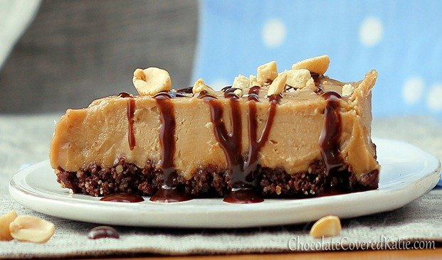 A slice of No-Bake Peanut Butter Pie on a plate with drizzled chocolate and nuts on top