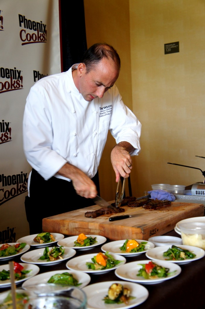 A chef cutting meat at the Phoenix Cooks event