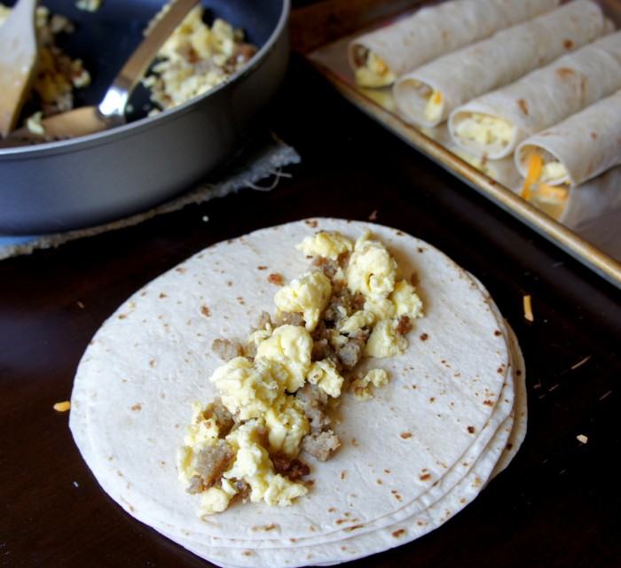 A tortilla with scrambled eggs and sausage laid out on top next to a pan of rolled up breakfast flautas