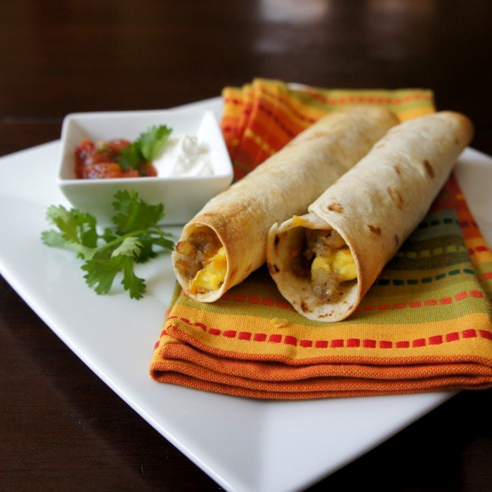 A close up of breakfast flautas displayed on a napkin next to a small bowl of toppings