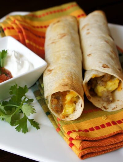 A close up of breakfast flautas displayed on a napkin, with sausage, egg and cheese in them