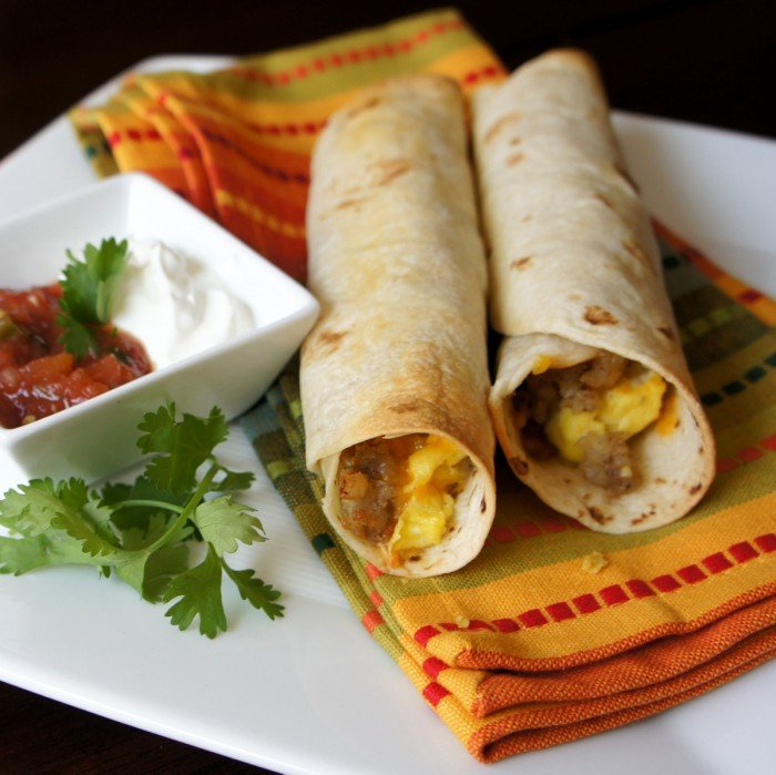 A close up of breakfast flautas displayed on a napkin