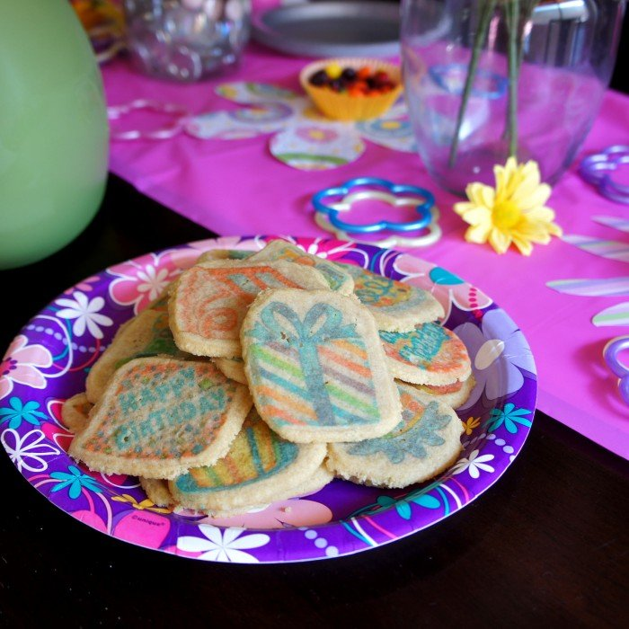 A plate of sugar cookies on a party plate surrounded by party birthday table decor