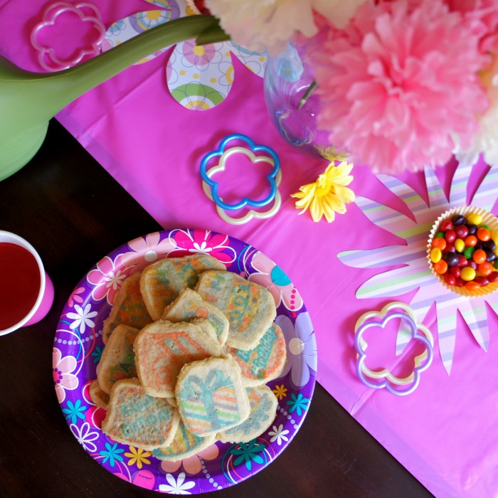 A look down on a plate of sugar cookies on a party plate surrounded by party birthday table decor