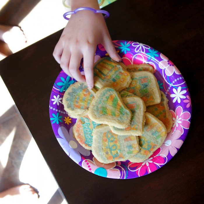 A hand taking a cookie from a plate of sugar cookies