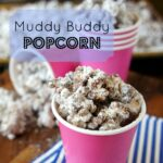 A pink cup full of Muddy Buddy Popcorn in front of other filled pink cups