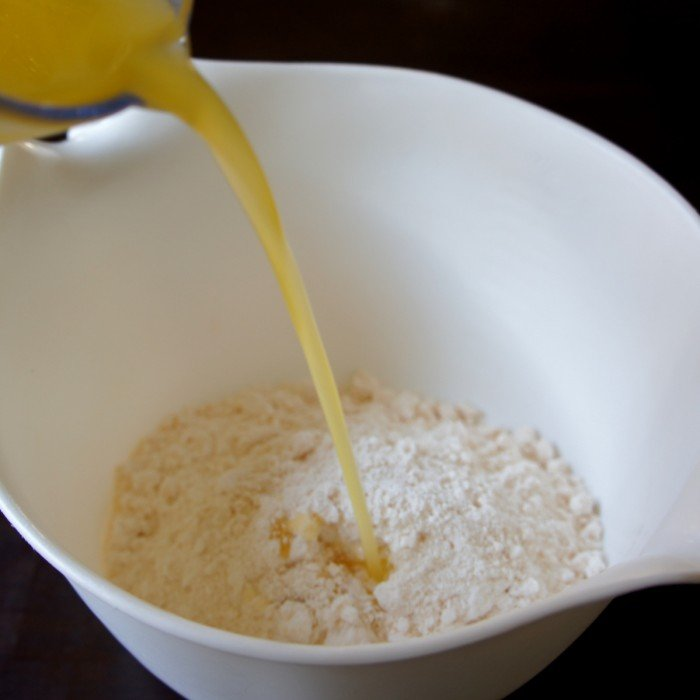 Liquid being poured into a  bowl of food with batter in it