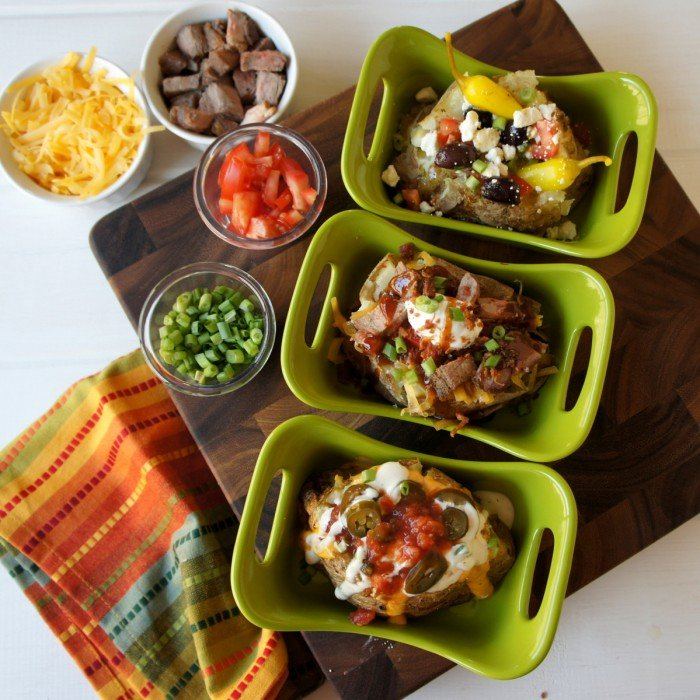 A look down on a three different baked potatoes with a variety of potatoes bar toppings