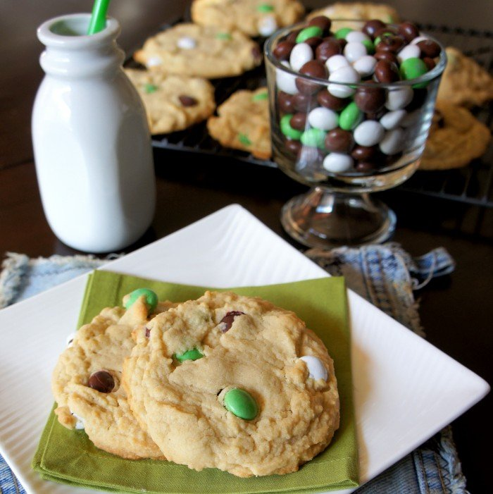 Two Coconut M&M Cookies on a green napkin on a plate next to a bowl of Coconut M&Ms and a small container of milk