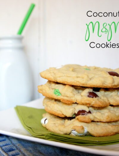 Four Coconut M&M Cookies stacked on top of each other on a plate