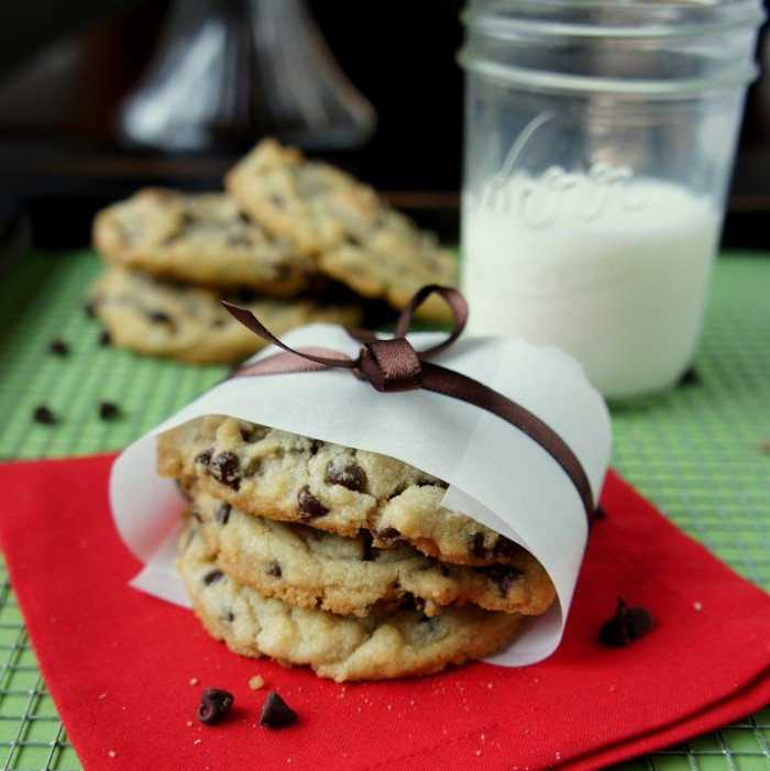 A display of three chocolate chip cookies wrapped with a bow in front of glass of milk and more cookies