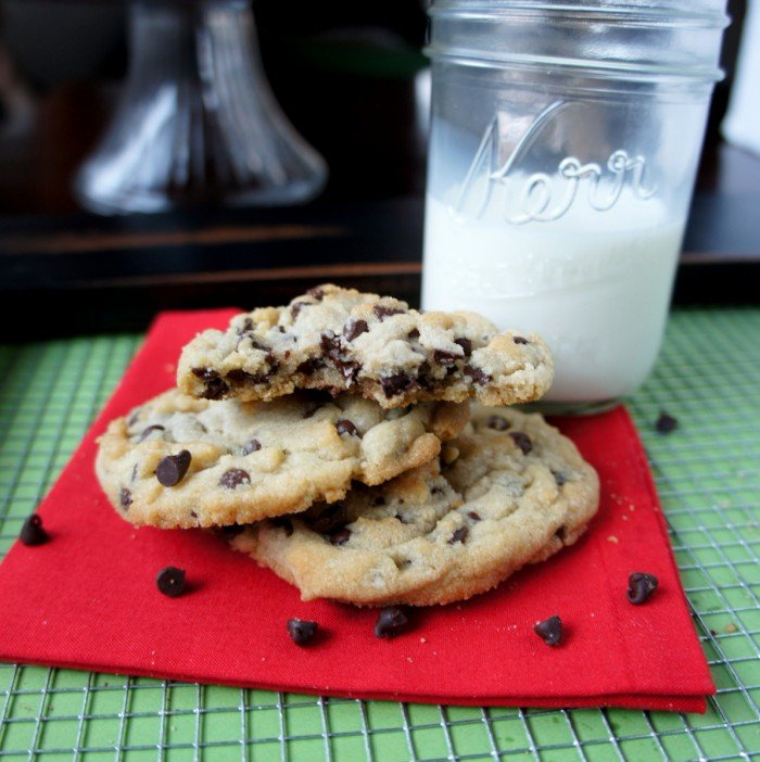 A smile pile of chocolate chip cookies, one with a few bites taken from it, next to a glass of milk