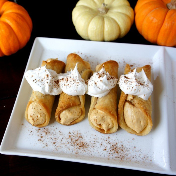 Four pumpkin pie cannolis on a plate topped with whipped cream and sprinkled with cinnamon
