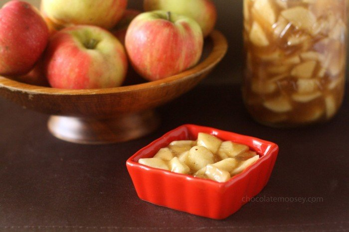 Homemade apple pie filling in a small dish in front of a bowl of apples and a jar of pie filling