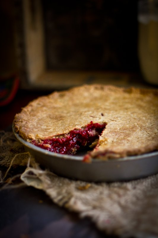 A raspberry pie with a slice removed from it showcasing an inside look