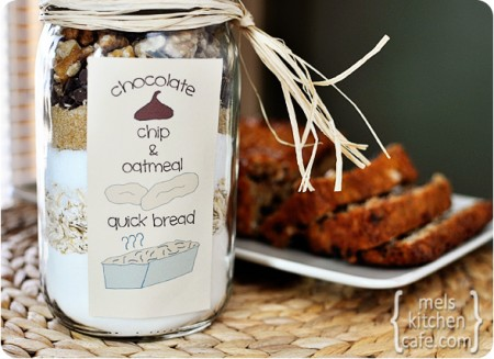 Oatmeal Chocolate Chip Quick Bread in a large mason jar in front of a sliced baked loaf of bread behind it