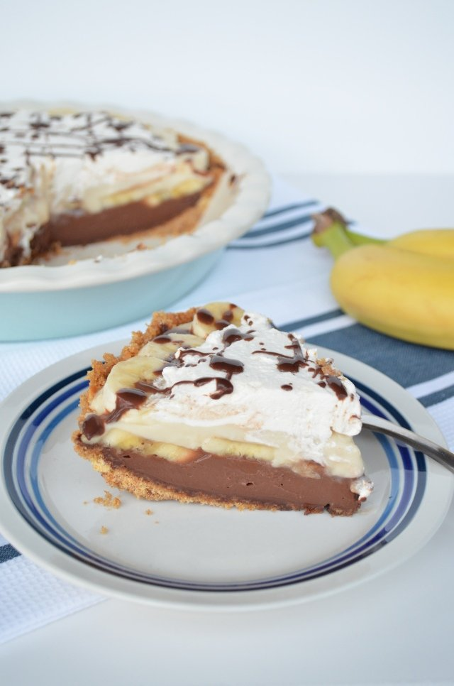 A slice of Black-Bottom Banana Cream Pie on a plate next to a couple of bananas and the full pie