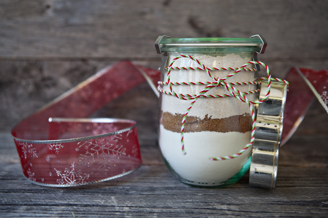 Gingerbread Cookie Mix in a a Jar displayed on a table next to some ribbon and a cookie cutter.
