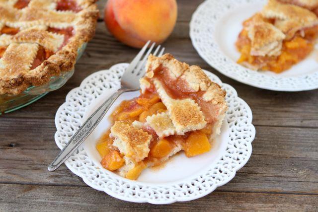 A slice of peach pie on a plate