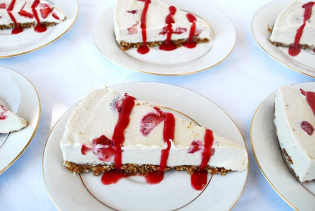 A slice of Strawberry Ice Cream Pie with drizzled strawberry sauce on top displayed on a plate
