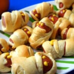 Mini Mummy Wrapped Hot Dogs on a plate with mustard eyeballs