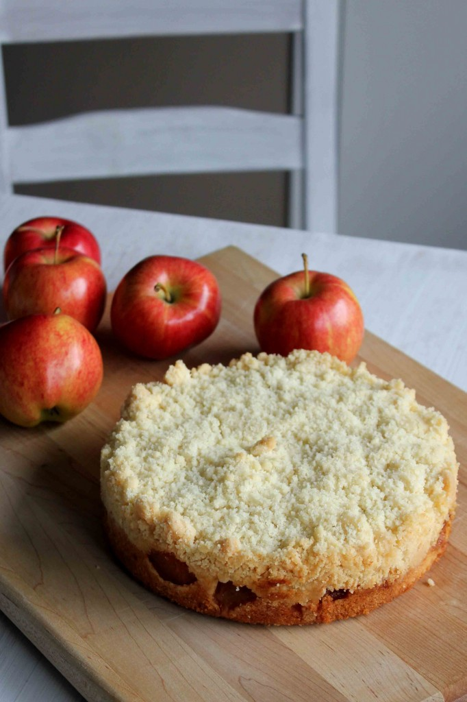 A display of Apple Crumble Cake in front of a small pile of apples