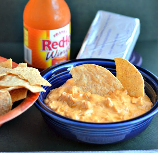 A chips dipped into a bowl of Buffalo Chicken Dip