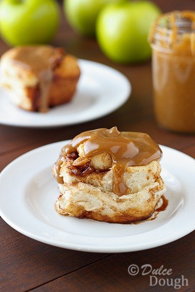 A close up of a Caramel Apple Cinnamon Roll displayed on a white plate on a table.
