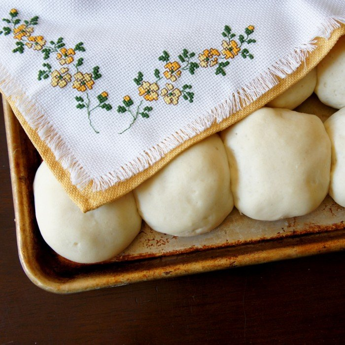 A pan of raising dough balls covered by a towel