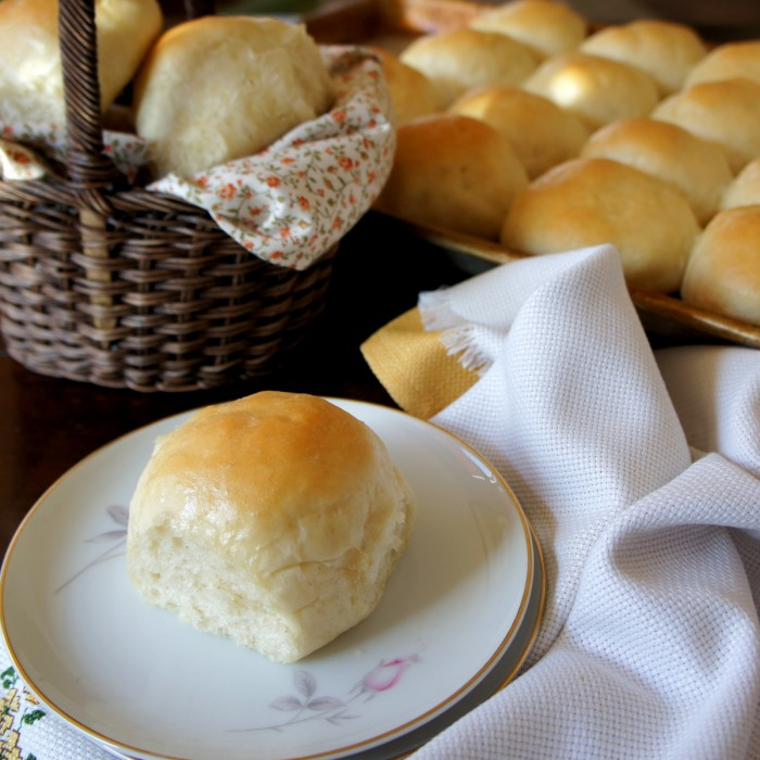 A plate with a baked roll on it in front of a basket and pan filled with baked rolls