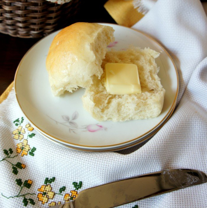 A baked roll sliced in half on a plate with a square of melting butter on one half