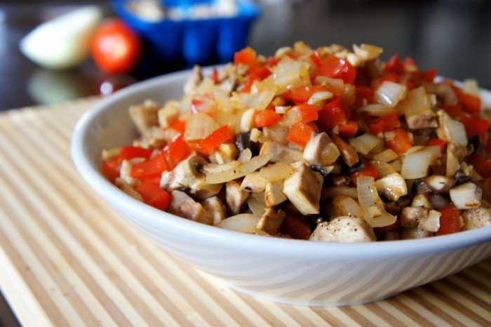 A bowl of cooked chicken, peppers and onions