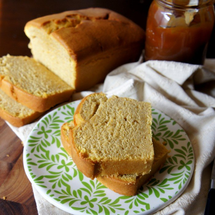 Two sliced of pound cake on a plate in front of the loaf they were sliced from