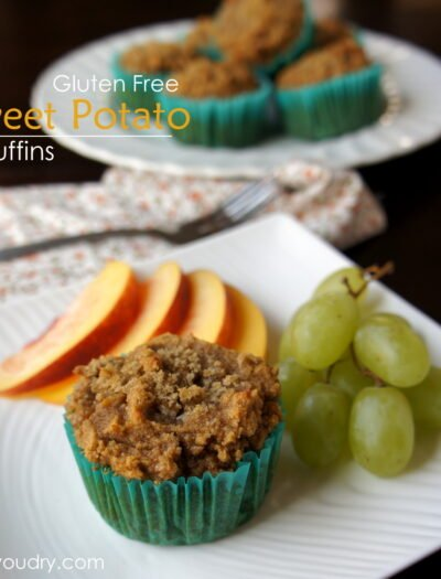 A plate with a Gluten Free Sweet Potato Muffin with a side of sliced peaches and a small bunch of grapes