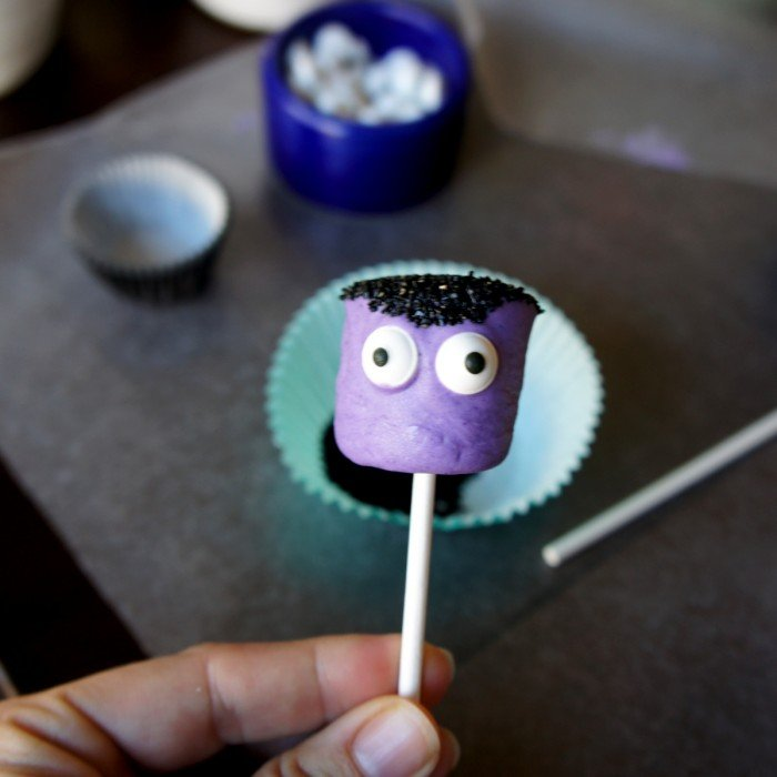 The front view of a purple dipped marshmallow pop with black sprinkles for hair and two candied eyes added