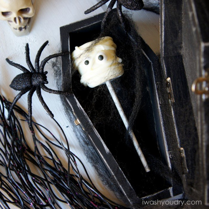 A display of a Mummy themed marshmallow pop in a coffin surrounded by other Halloween decorations