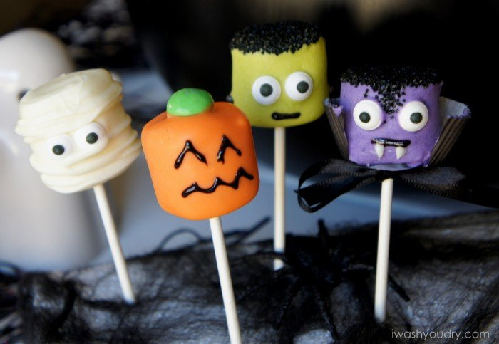 A close up of Halloween themed Marshmallow pops - a mummy, a pumpkin, Frankenstein and a vampire