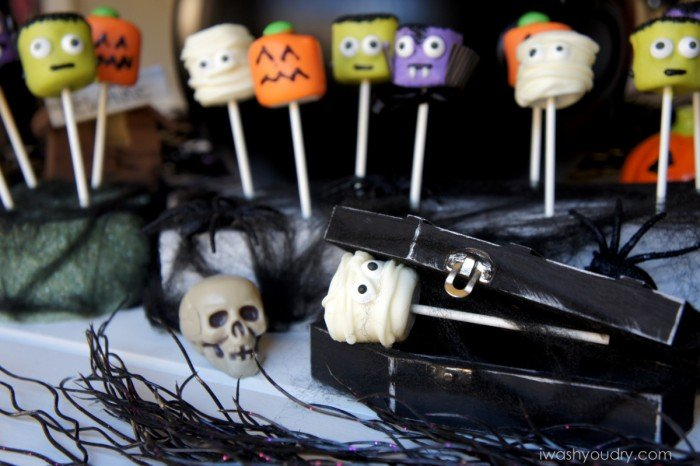 A display of Halloween themed marshmallow pops, surrounded by other Halloween decor