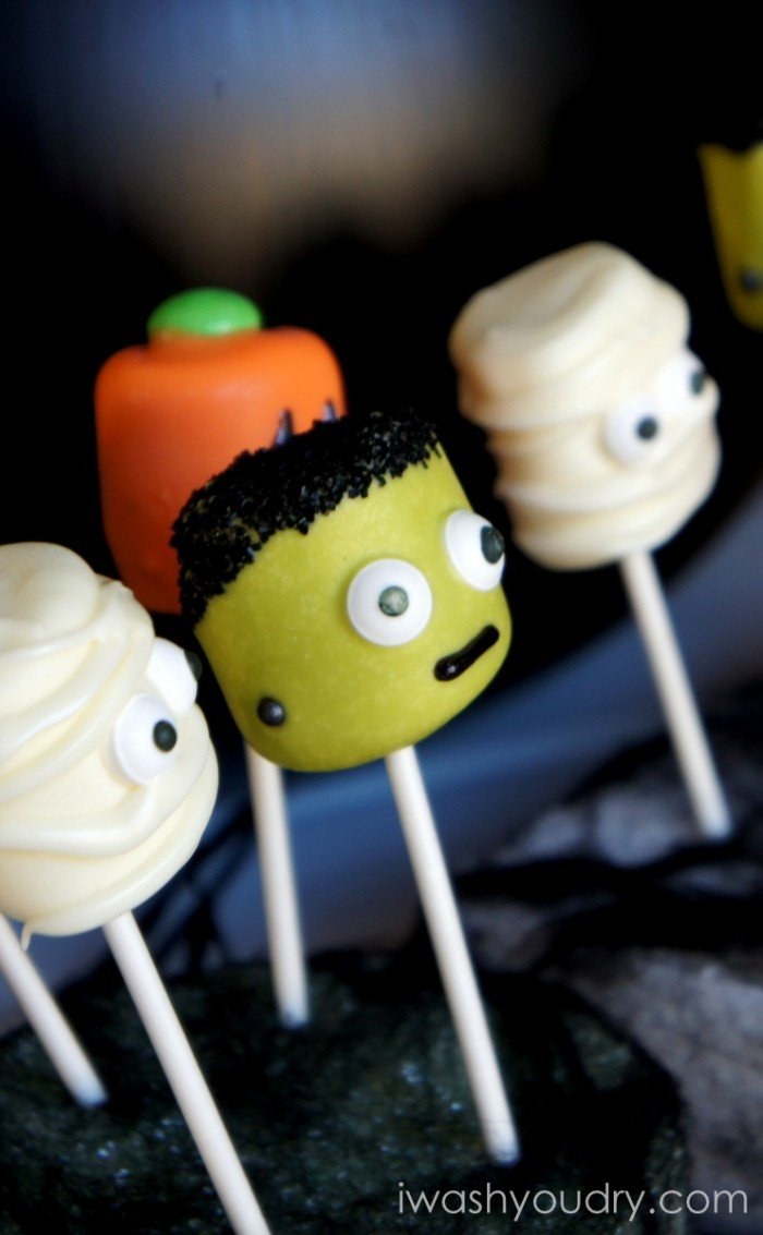 A close up side view of Halloween themed Marshmallow pops - a mummy, a pumpkin, Frankenstein and another mummy